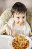 Bambino che mangia gli spaghetti con le verdure Bambino divertendosi cibo Ragazzo dai capelli di Brown con il fronte coperto in s immagine stock libera da diritti