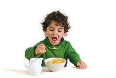 Bambino che mangia i fiocchi di granturco fotografie stock libere da diritti