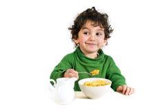 Bambino che mangia i fiocchi di granturco Immagini Stock
