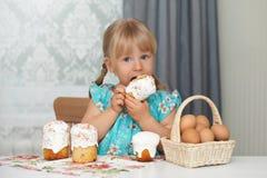 Bambino che mangia il dolce e le uova di pasqua Fotografia Stock Libera da Diritti