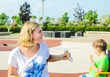 Bambino che mangia il gelato all'aperto nel parco del gioco Immagini Stock