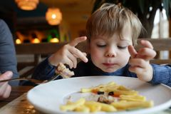 Bambino che mangia le patate fritte Fotografia Stock Libera da Diritti