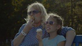 Bambino che mangia mangiando gelato con la nonna all'aperto stock footage