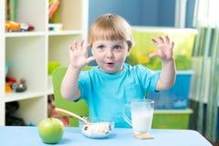Bambino che mangia mela alla cena in scuola materna a casa Fotografie Stock