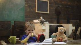 Bambino che mangia mela succosa Il ragazzo biondo ha resto fra le lezioni Il ragazzo biondo ha resto e mela del cibo sull'aula de video d archivio