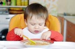 Bambino che mangia minestra sulla cucina Immagini Stock Libere da Diritti