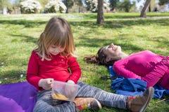 Bambino che mangia pasta in parco accanto alla madre Fotografia Stock
