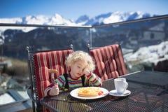Bambino che mangia pranzo doposci Divertimento della neve di inverno per i bambini Fotografie Stock