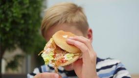 Bambino che mangia un panino con il pollo, il formaggio ed i verdi in un fast food stock footage