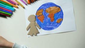 Bambino che mette il segno della famiglia e del cuore della carta vicino alla pittura della terra, pianeta di risparmio video d archivio