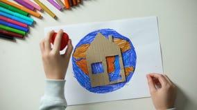 Bambino che mette la casa della carta ed il segno del cuore vicino alla pittura della terra, mondo la nostra casa archivi video