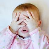 Bambino che mette le mani sul fronte Fotografie Stock