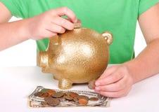 Bambino che mette soldi nella banca piggy Immagini Stock Libere da Diritti