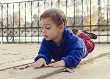 Bambino che mette su esterno al suolo fotografia stock