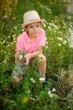 Bambino che mette sull'erba con le margherite immagini stock libere da diritti