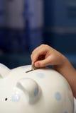 Bambino che mette una moneta nel porcellino salvadanaio Immagini Stock Libere da Diritti