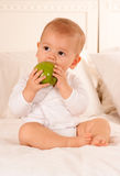 Bambino che morde una mela Immagine Stock