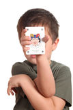 Bambino che mostra la scheda di gioco del burlone Immagine Stock