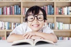 Bambino che mostra un sorriso a trentadue denti nella biblioteca Fotografia Stock Libera da Diritti