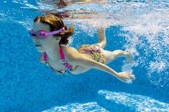 Bambino che nuota underwater nel raggruppamento Fotografie Stock
