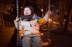 Bambino che oscilla alla notte Fotografie Stock