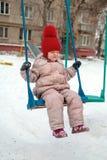 Bambino che oscilla su un'oscillazione nel campo da giuoco fotografie stock libere da diritti