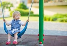 Bambino che oscilla sull'oscillazione sul campo da giuoco. Vista laterale Immagine Stock