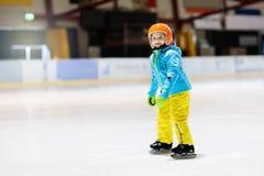 Bambino che pattina sulla pista di pattinaggio sul ghiaccio dell'interno Pattino dei bambini fotografia stock libera da diritti