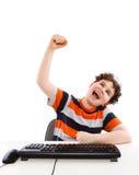 Bambino che per mezzo del calcolatore su priorità bassa bianca Fotografia Stock