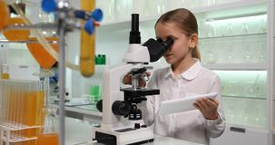 Bambino che per mezzo della compressa, microscopio nel laboratorio di chimica della scuola, scienza di lavoro 4K della ragazza stock footage