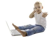 Bambino che per mezzo di un telefono cellulare e di un computer portatile Immagini Stock