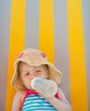 Bambino che pone sulla base del sole e che beve dalla bottiglia Fotografia Stock Libera da Diritti