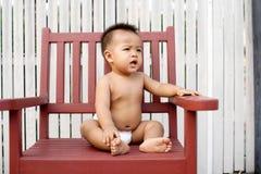 Bambino che pone sulla presidenza Fotografie Stock Libere da Diritti