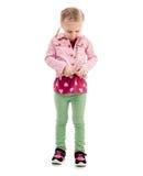 Bambino che prova a zippare il suo cappotto rosa, isolato Immagini Stock