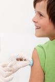Bambino che riceve vaccino con il sorriso sul suo fronte immagine stock libera da diritti