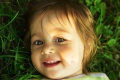 Bambino che riposa su un'erba verde Fotografie Stock