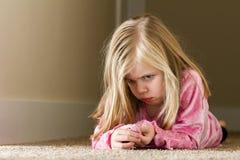 Bambino che risiede nel corridoio triste Immagine Stock