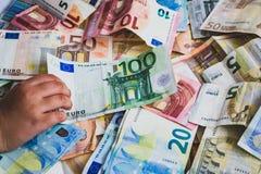 Bambino che ruba cento banconote dell'euro sulle banconote più euro fotografie stock libere da diritti
