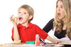 Bambino che rubacchia un morso della pasta del biscotto Fotografia Stock