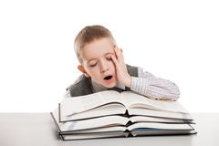 Bambino che sbadiglia sui libri di lettura Immagini Stock
