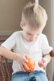 Bambino che sbuccia arancia Fotografia Stock