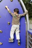 Bambino che scala al campo da giuoco Fotografie Stock
