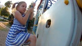 Bambino che scala sulla parete rampicante Neonata che gioca i giochi degli sport dei bambini sul campo da giuoco video d archivio