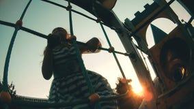 Bambino che scala sulla parete rampicante Neonata che gioca i giochi degli sport dei bambini sul campo da giuoco archivi video