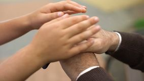 Bambino che segna le mani dell'uomo anziano, programma di sostegno sociale per i pensionati, gentilezza archivi video