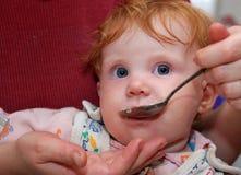 Bambino che si alimenta con il cucchiaio. Primo piano Fotografia Stock