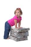 Bambino che si appoggia contro le pile di giornale Fotografia Stock