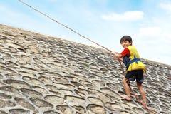 Bambino che si arrampica usando corda Immagini Stock Libere da Diritti