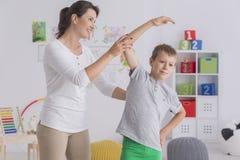 Bambino che si esercita con il fisioterapista femminile Fotografie Stock