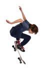 Bambino che si esercita in un trucco sul pattino Fotografia Stock